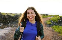 Glückliche wandernde Frau, welche die oben lächelnden Daumen gibt Junges Wandererfrauenlächeln froh an der Kamera im Freien auf W stockbild