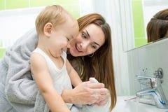 Glückliche waschende Hände der Mutter und des Kindes mit Seife herein Lizenzfreies Stockfoto