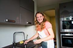 Glückliche waschende Schale der jungen Frau. Stockfotografie
