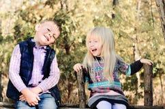 Glückliche weiße Kinder, die auf hölzernem Garten-Zaun sitzen stockbilder
