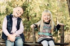 Glückliche weiße Kinder, die auf hölzernem Garten-Zaun sitzen stockfotografie