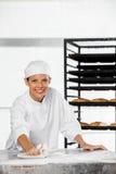 Glückliche weibliche Bäcker-Cleaning Flour From-Tabelle Stockbilder