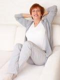 Glückliche weibliche Frau auf Sofa Stockfoto