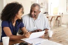 Glückliche weibliche Gesundheitswesenarbeitskraft, die bei Tisch das Lächeln mit einem älteren Mann während eines Hauptgesundheit stockbild