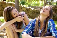 Glückliche weibliche Jugendliche, die Spaß im Park im Sommer habend lachen lizenzfreie stockfotos
