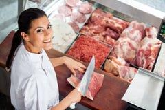 Glückliche weibliche Metzger-Cutting Meat At-Schlächterei Stockfoto