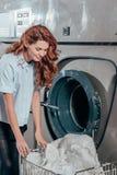 glückliche weibliche Trockenreinigungsarbeitskraft, die Kleidung aus nimmt stockfotos