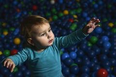 Glückliche wenig Kinderspiele auf einem Spielplatz füllten mit buntem pl lizenzfreie stockfotografie