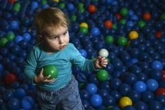 Glückliche wenig Kinderspiele auf einem Spielplatz füllten mit buntem pl stockfotos