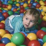 Glückliche wenig Kinderspiele auf einem Spielplatz füllten mit buntem pl stockfotografie