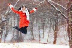 Glückliche Winter-Frau, die in den Schnee springt Lizenzfreie Stockfotos