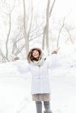 Glückliche Winterfrau, die im Schnee spielt Stockfotografie