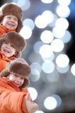 Glückliche Winterkinder gegen bunte Leuchten Stockfotos