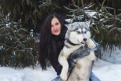 Glückliche Winterzeit der frohen jungen Frau, die mit nettem heiserem Hund im Schnee auf Straße spielt Lizenzfreie Stockbilder