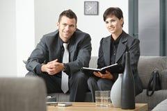 Glückliche Wirtschaftler, die im Büro sich treffen Stockfotos