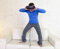 Glückliche Wohnzimmer-Sofacouch des Mannes zu Hause aufgeregt unter Verwendung der Schutzbrillen 3d, die virtuelle Realität 360 a Lizenzfreie Stockbilder
