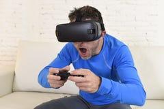 Glückliche Wohnzimmer-Sofacouch des Mannes zu Hause aufgeregt unter Verwendung der Schutzbrillen 3d, die virtuelle Realität 360 a Stockfoto