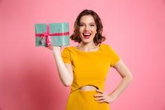 Glückliche ypung Frau mit der Hand auf ihrer Taille, die Geschenkbox, Blick hält Stockbild
