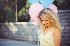 Glückliche zarte junge Frau mit buntem Latex steigt im Ballon auf und hält ihr Kleid, städtische Szene, draußen lizenzfreie stockbilder