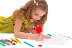 Glückliche Zeichnung des kleinen Mädchens in einem Album Stockbilder