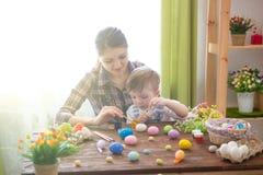 Glückliche Zeit beim Malen von Ostereiern Junges Küken in Wanne, 2 malte Eier und Blumen Glückliche Mutter und ihr nettes Kind, d lizenzfreie stockfotografie