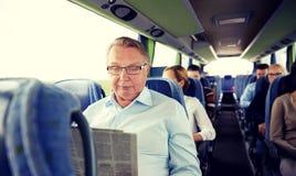 Glückliche Zeitung des älteren Mannes Leseim Reisebus stockfotos