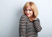 Glückliche zufällige blonde Frau mit der Kurzhaarfrisur, die mit Lächeln schaut Stockfoto