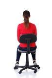 Glückliche zufällige Frau, die auf einem Stuhl sitzt. Hintere Ansicht. stockbild