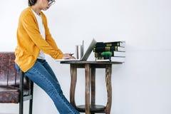 Glückliche zufällige junge asiatische Frau, die in Haupt- oder kleinem Büro w arbeitet lizenzfreies stockbild