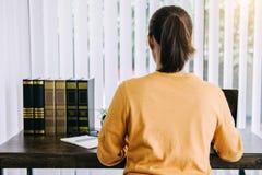 Glückliche zufällige junge asiatische Frau, die in Haupt- oder kleinem Büro w arbeitet stockfotos
