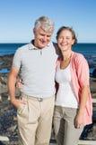 Glückliche zufällige Paare, die an der Kamera durch die Küste lächeln Stockfotografie