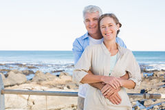 Glückliche zufällige Paare, die durch die Küste umarmen Stockfotografie