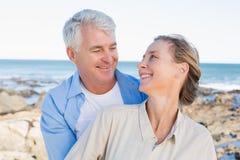 Glückliche zufällige Paare, die durch die Küste umarmen Lizenzfreie Stockfotografie