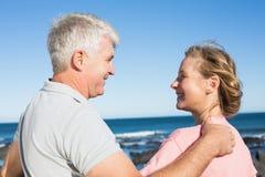 Glückliche zufällige Paare, die an einander durch die Küste lächeln Lizenzfreie Stockbilder