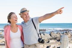 Glückliche zufällige Paare, die etwas durch die Küste betrachten Stockfoto