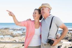Glückliche zufällige Paare, die etwas durch die Küste betrachten Stockfotografie