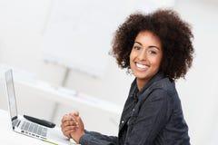 Glückliche zufrieden gestellte junge Frau mit einer Afrofrisur Stockfoto