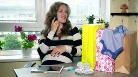 Glückliche zukünftige Mutter, die online am Telefon nach dem erfolgreichen Einkaufen auf Internet spricht stock video