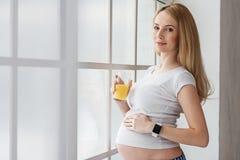 Glückliche zukünftige Mutter, die zu Hause Tag genießt Stockfotos