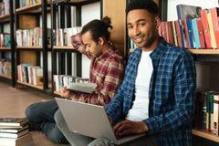 Glückliche zwei afrikanische Mannstudenten, die Laptop-Computer verwenden stockfotografie