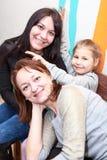 Glückliche zwei Erwachsene Frauen und junges hübsches Mädchenschießen mit Hörnern über Köpfen Stockfoto