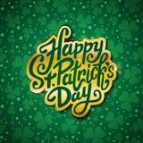 Glücklichen St Patrick Tageshandgeschriebene Mitteilung, Bürstenstiftbeschriftung im Gold auf grüner Shamrockhintergrundpostkarte Stockfoto