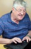 Glücklicher Älterer, der seinen Laptop verwendet. Stockbild
