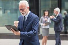 Glücklicher älterer Geschäftsmann, der die Tablette, stehend vor einem Bürogebäude verwendet stockbild