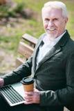 Glücklicher älterer Geschäftsmann, der Kaffee genießt stockfotos