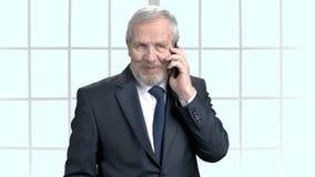 Glücklicher älterer Geschäftsmann, der am Telefon spricht stock footage