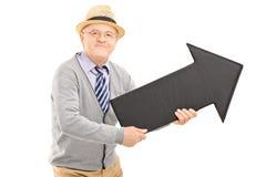 Glücklicher älterer Herr, der einen großen schwarzen Pfeil hält Stockfoto