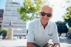 Glücklicher älterer Mann, der draußen in der Stadt sitzt Stockbilder