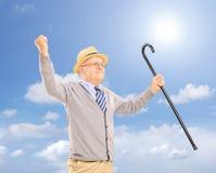 Glücklicher älterer Mann, der einen Stock hält und draußen Glück gestikuliert Stockfoto
