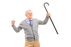 Glücklicher älterer Mann, der einen Stock hält und Glück gestikuliert Stockfoto